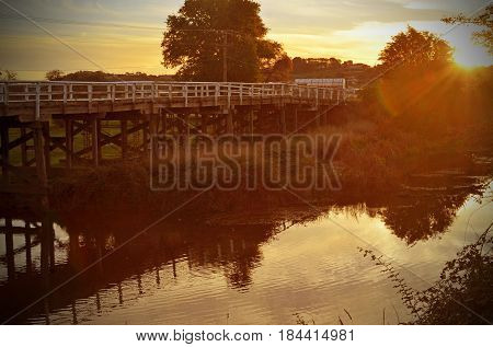 Tranquil scene of an old wooden bridge over a river at sunset in Goulburn, NSW, Australia