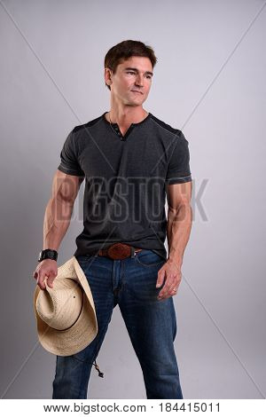 The tough cowboy is showing off his buff arms.
