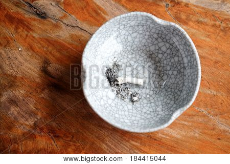 cigarette butts in ashtrays on wood table, top view