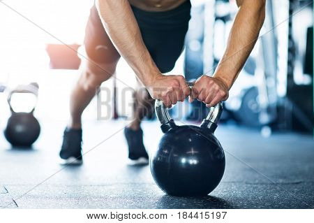 Unrecognizable young fit man doing strength training, doing push ups on kettlebells in modern gym.