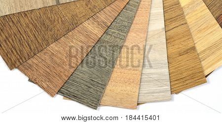 Samples of vinyl and laminate on brown wooden texture