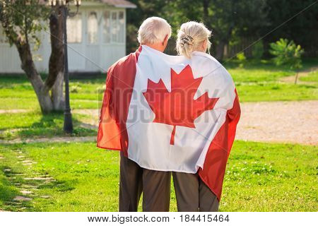 Old couple wrapped in flag. Back view of two people. Life in immigration.