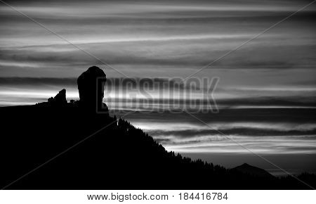 Silhouette of Roque Nublo and cloudy sky at nightfall, Gran canaria, Canary islands