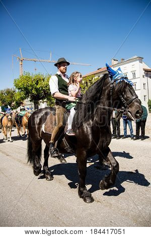 Tittmoning,Germany-April 30,2017: A rider with a little girl at the annual St.George's parade