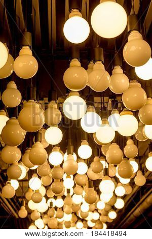 Group of Edison light bulbs hanged from ceiling in department store.