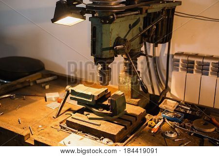 Workplace with a drill and vice. Work at a factory on drill. Drill machine. Mechanic drill
