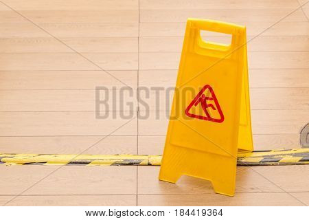 Slippery icon on yellow plastic warning sign alerts for hazard on floor under construction concept.