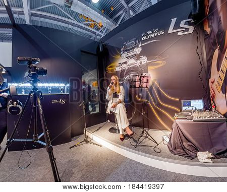 MOSCOW RUSSIA - APRIL 21 2017: Unidentified singer demonstrates LS-100 stereo audio recorder at Art Space booth of Olympus company at PhotoForum 2017 trade show in Moscow Russia on April 21 2017.