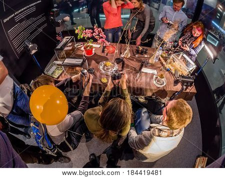 MOSCOW RUSSIA - APRIL 21 2017: Visitors take part in macro photography workshop at booth of Olympus company at PhotoForum 2017 trade show and exhibition in Moscow Russia on April 21 2017.