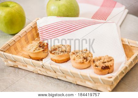 Magnificent portioned shortbread baskets with sweet stuffing. Professional baking. Background of a wicker basket and a white dish towel