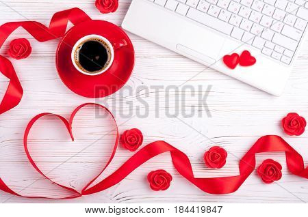 Valentines background with red heart coffee cup candy laptop and roses. Valentines Day greeting card. Female workplace. Top view
