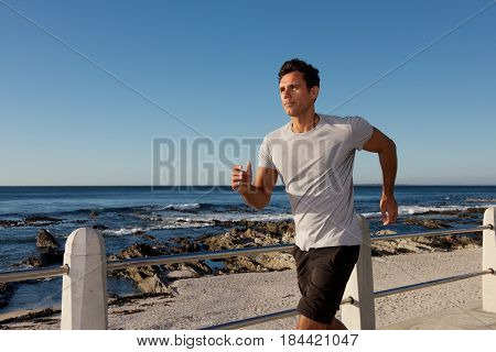 Active Middle Age Man Jogging Outside By Sea