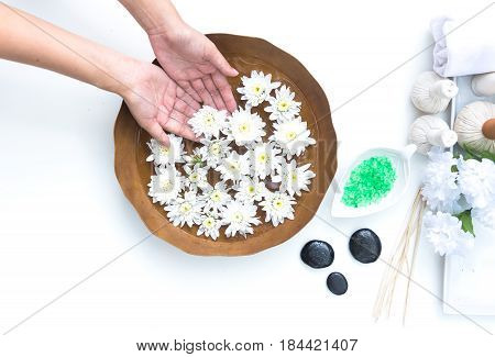 Spa treatment and product for hand and foot spa with flowers and water wooden background;