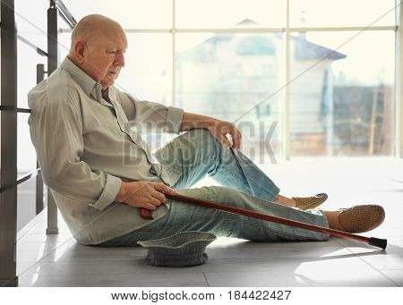 Senior man with hat asking for handout while sitting near banisters. Poverty concept