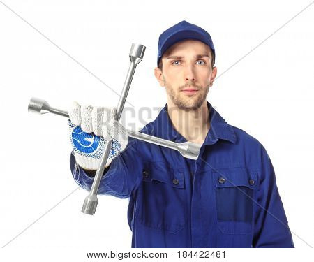 Handsome auto mechanic with wheel wrench on white background