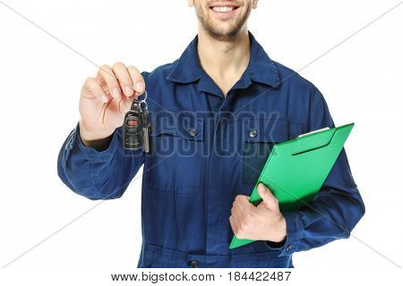 Auto mechanic with car key and clipboard on white background, closeup