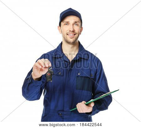 Handsome auto mechanic with car key and clipboard on white background