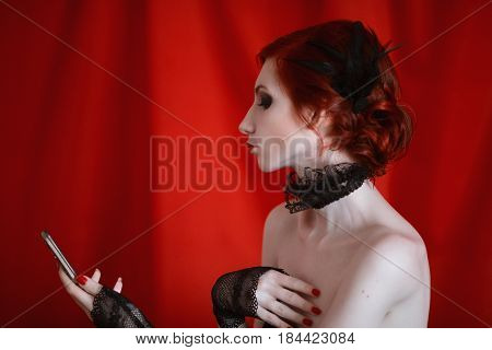 Woman actress with red curly hair in a black dress and retro makeup looks in the mirror on red background. Red-haired actress girl with pale skin blue eyes unusual appearance red lips and a fatal face. Noir actress. Retro actress