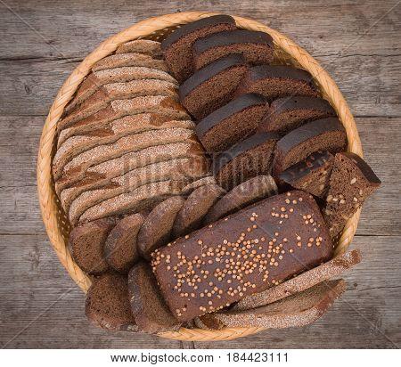 Wicker Basket, Breadbasket, Bread-plate With Slices Of Dark Bread On Rustic Wooden Boards Background