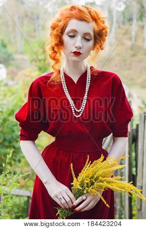 Stylish woman with red hair and a red slinky stylish dress with a bouquet of yellow flowers in hand. Red-haired stylish girl with pale skin blue eyes and bright unusual appearance with a necklace of beads around her neck. Stylish model. Stylish retro look