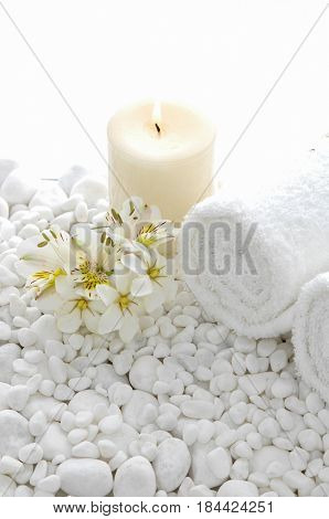 gardenia with candle ,rolled towel on white pebbles