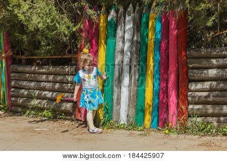 Girl near the fence, made in the form of multi-colored pencils