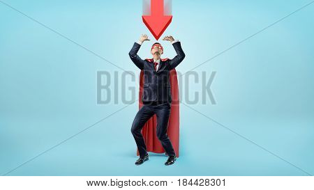 A businessman in a red cape and a mask cowering under a large red arrow pointing down at him. Business troubles. Unexpected problems. Recession.