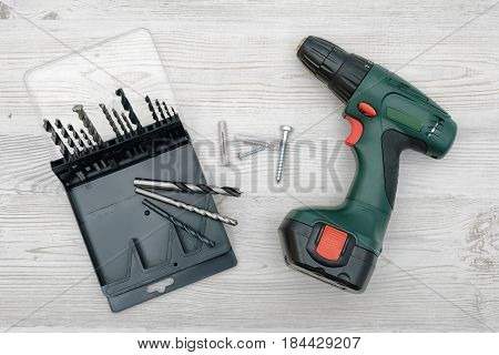 A cordless drill set to stand on a wooden table background with a set of bits in the box. Manual labor. Home improvement. Handyman tools.