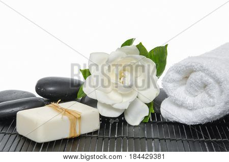 Rolled towel, black stones and gardenia,soap on bamboo mat