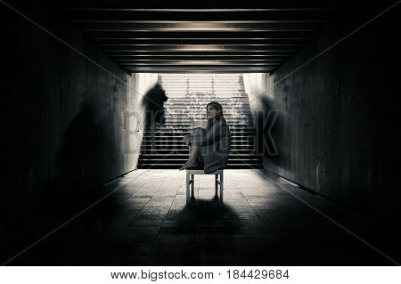 Young woman alone in a tunnel and strangers pass beyond. Conception of loneliness
