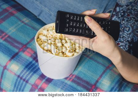 Girl Watching Tv With Popcorn At Home In The Living Room. The Concept Of Laziness