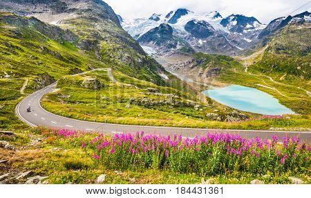 Beautiful view of motorcyclist driving on winding mountain pass road in the Alps through gorgeous scenery with mountain peaks glaciers lakes and green pastures with blooming flowers in summer