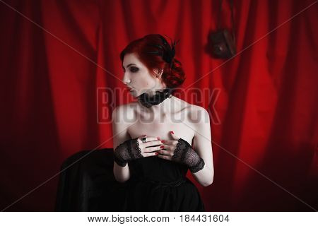 Vintage woman with red curly hair in a black vintage dress and retro makeup on a red background. Red-haired vintage girl with pale skin blue eyes a bright unusual appearance red lips and a fatal face. Noir vintage woman. Vintage model