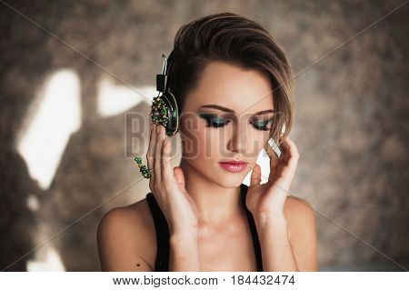 Lovely girl with tanned skin and white hair listening to music on headphones. Female beauty portrait of a beautiful makeup. Enjoying good music. Music concept. Listen music. Joy by music. Music in radio