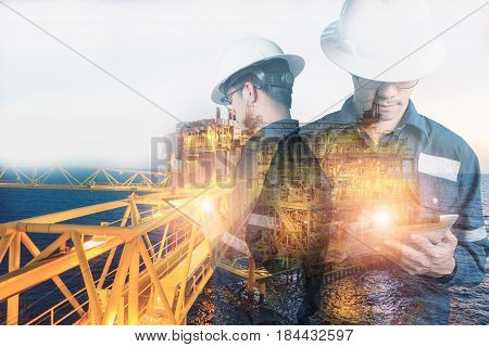 Double exposure of Engineer or Technician man with safety helmet operated platform or plant by using tablet with offshore oil and gas platform background for oil and gas business concept