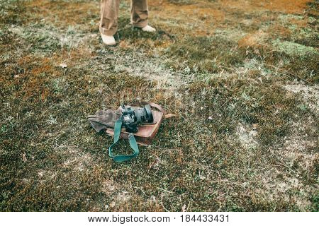 Leather Bag With Gloves And Camera Lying In Field. Legs Of Man In Background.