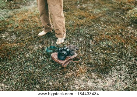 Man Standing Next To Leather Bag With Gloves And Camera Lying In Field. High Angle View.