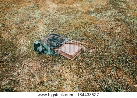Leather Bag With Gloves And Camera Lying In Meadow. High Angle View.