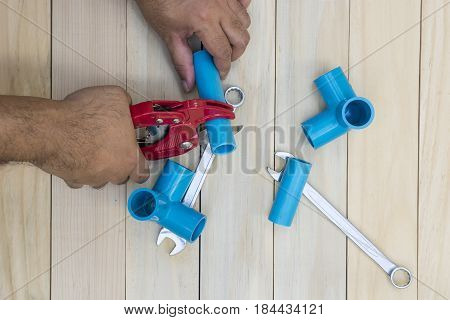 abstract plumber cutting the blue tube with red tools on wood background - can use to display or montage on product