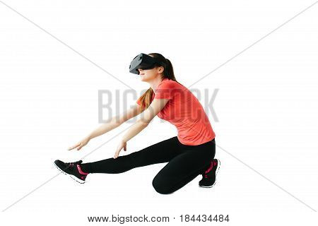 A young beautiful woman in virtual reality glasses makes aerobics remotely. Future technology concept. Modern imaging technology. Classes in single sports remotely. On a white background.