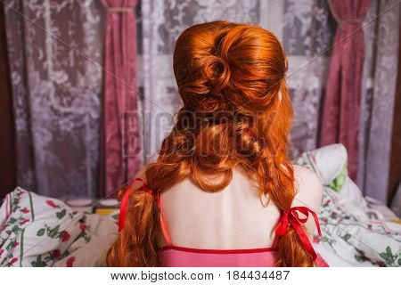 Woman with long red curly hair gathered into braids and nightgown in bed under blanket. Red-haired girl is sitting back to camera in bedroom on the bed. Updo