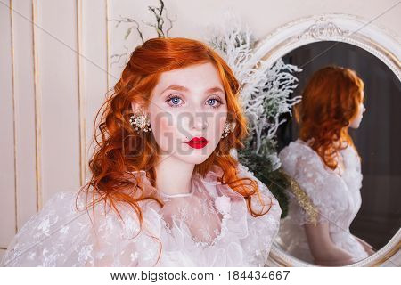 Pretty woman with long red curly hair in a white vintage wedding pretty dress with white pearl earrings on her ears. Red-haired pretty girl with pale skin, blue eyes, a bright unusual appearance in the luxurious bedroom. Pretty model