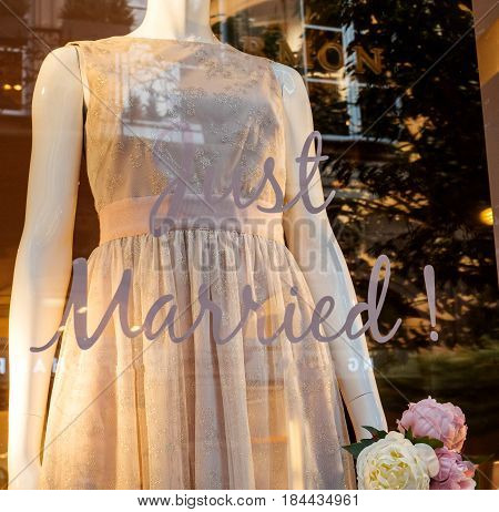 Just Married tag on show-window of a French fashion boutique with short elegant silk wedding dress