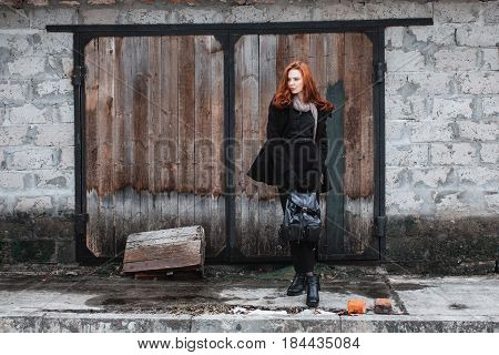 Striking trendy girl with long red hair in black clothes. A trendy woman in a black trendy coat and backpack in hands posing on the background of old wall. Female street fashion style. Beautiful elegant redhead trendy model