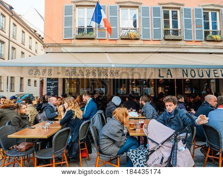 STRASBOURG FRANCE - APR 27 2017: Exterior of the famous authentic French La Nouvelle Poste brasserie restaurant bar in central Strasbourg with large crowd of people having fun drinking cafe beers smoking outside terrace