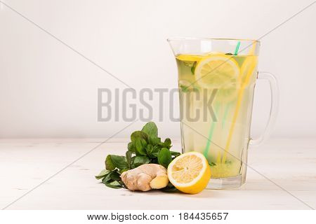 A glass decanter with a summer refreshing lemonade made of lemons and ginger with mint added on a white wooden background. Detox water. Ingredients. Cleaning the body of toxins, vitamins
