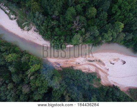 Drone photo. Top view of the pebbled beach and the bend in the river in the forest.