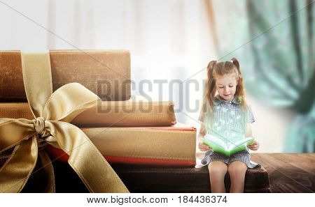 Adventure story and fairy tale. Tiny girl with books and magic glowing on table