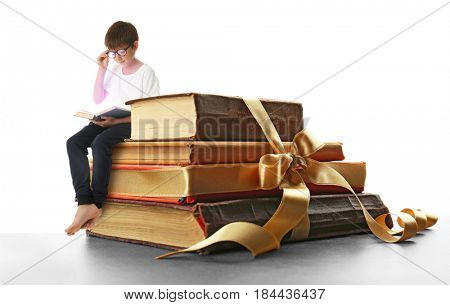 Adventure story and fairy tale. Tiny boy with books and magic glowing on white background