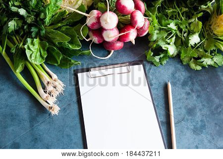 A Bunch Of Radishes, Young Green Garlic, Spinach And Parsley Lie On A Blue Background.